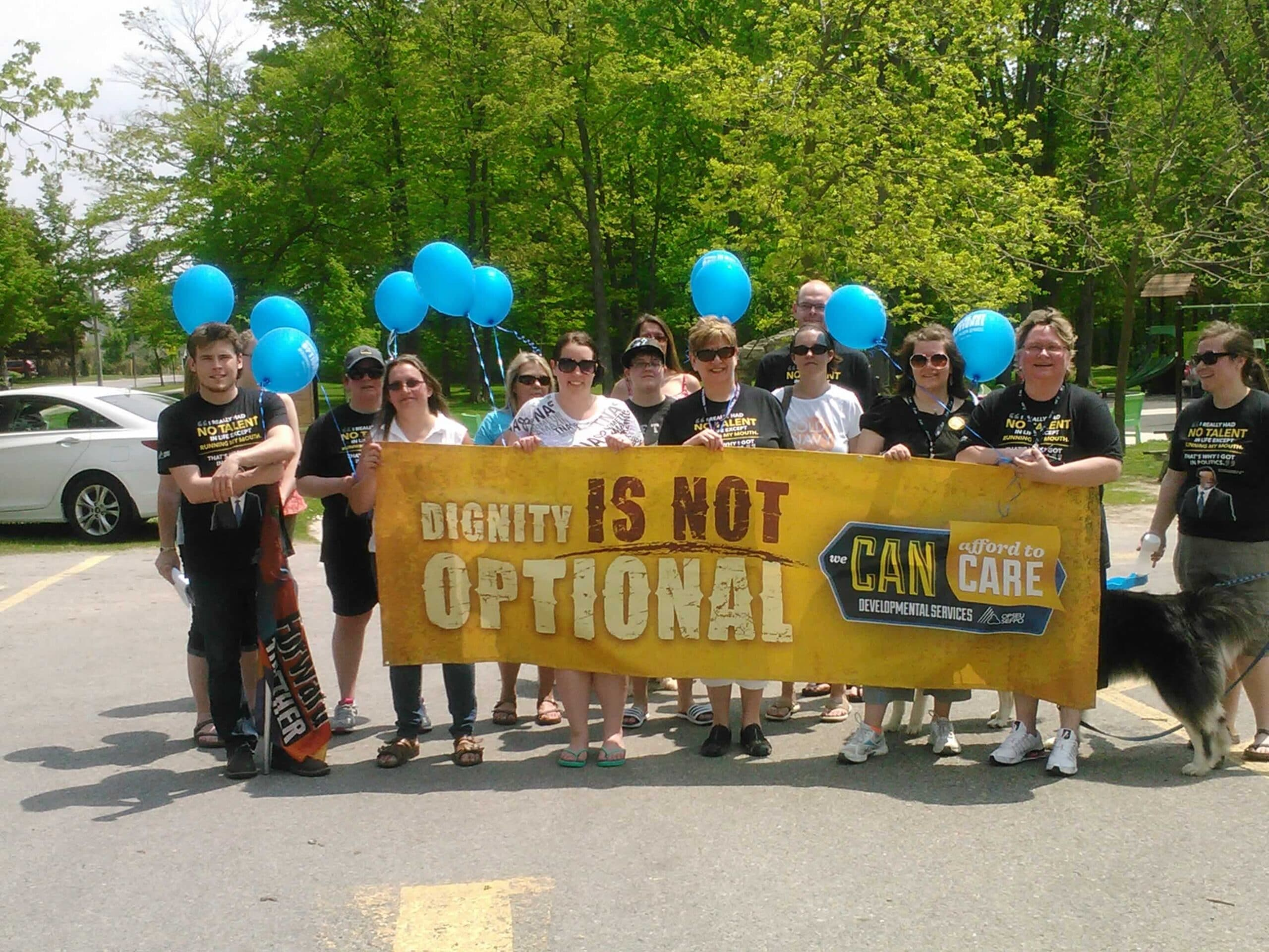 OPSEU members hold up balloons & banner that says: Dignity is not optional