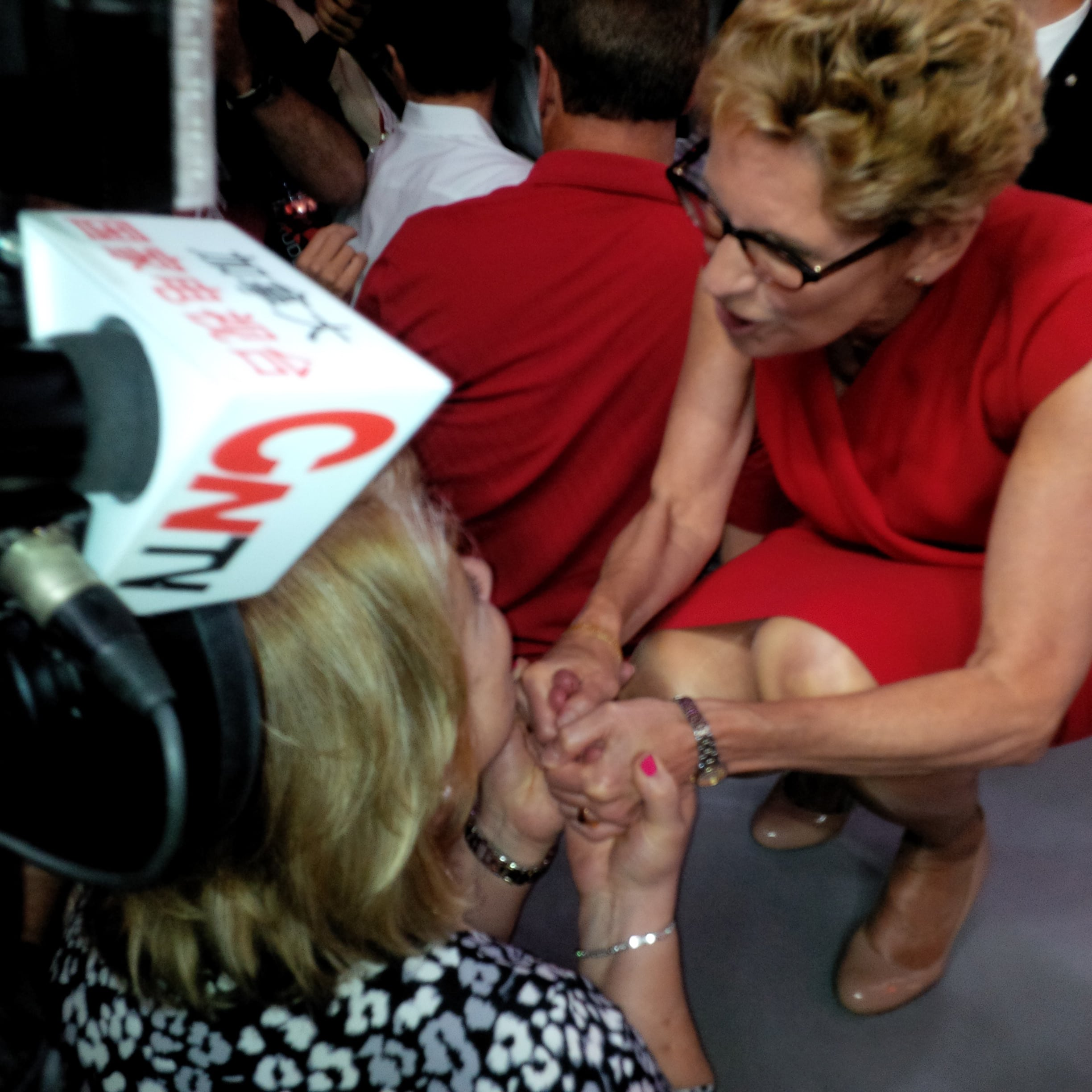 Kathleen Wynne talking to someone while a news station records the interaction