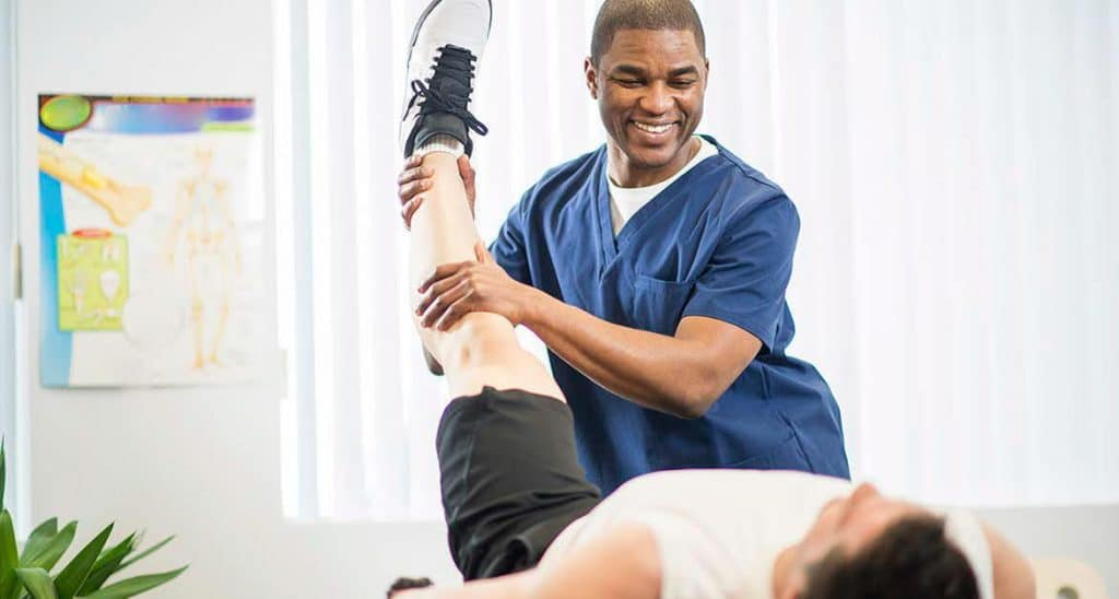 Male physiotherapist helping patient