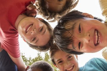 Group of five children arm-in-arm smiling into the camera.