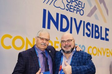 OPSEU President Warren (Smokey) Thomas and First Vice-President/Treasurer Eduardo (Eddy) Almeida arm-in-arm and show thumbs-up during Convention 2019.