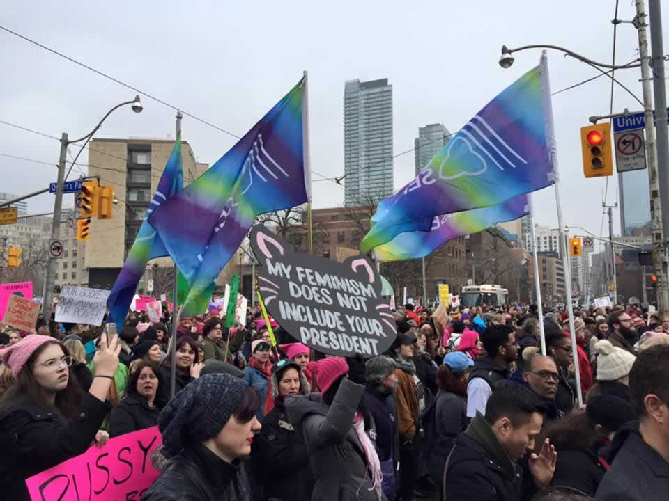 OPSEU members holding OPSEU flags during crowded Women's March in Toronto.