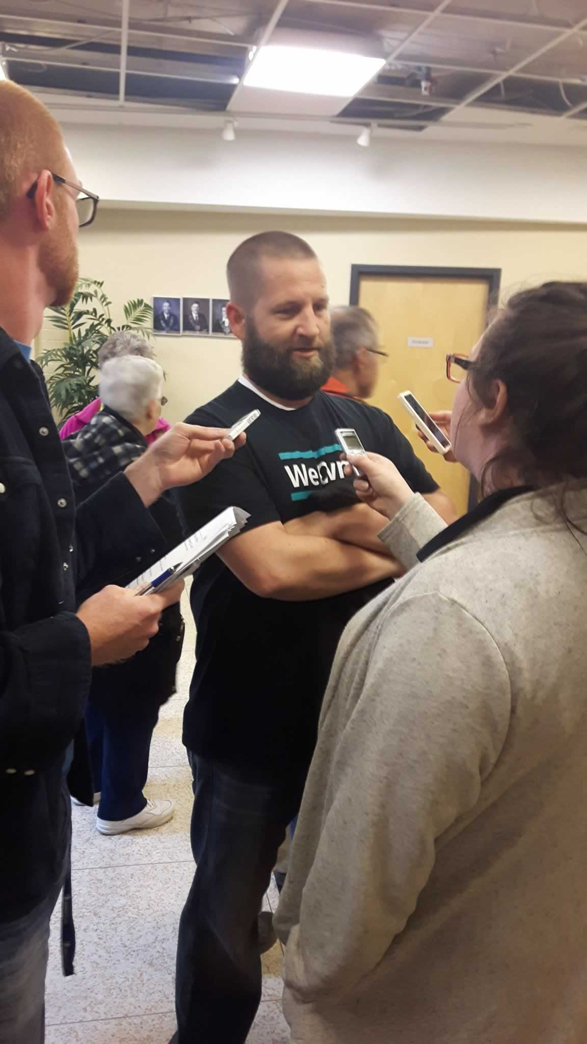 OPSEU member wearing We Own It shirt talks to reporters about Save Grey Gables campaign
