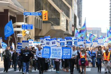"""Large group of OPSEU members holding signs, flags, and a """"Quality Public Services"""" banner march in downtown Toronto during Convention 2015"""