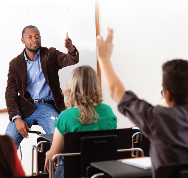 Classroom teacher gestures to a student with their hand raised.