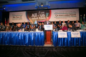 OPSEU President Warren (Smokey) Thomas introducing the We Own It mobilizers standing behind him onstage during Convention 2017 Day 1