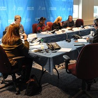 OPSEU members and staff sitting at at a table wearing headsets during a Corrections teletown hall