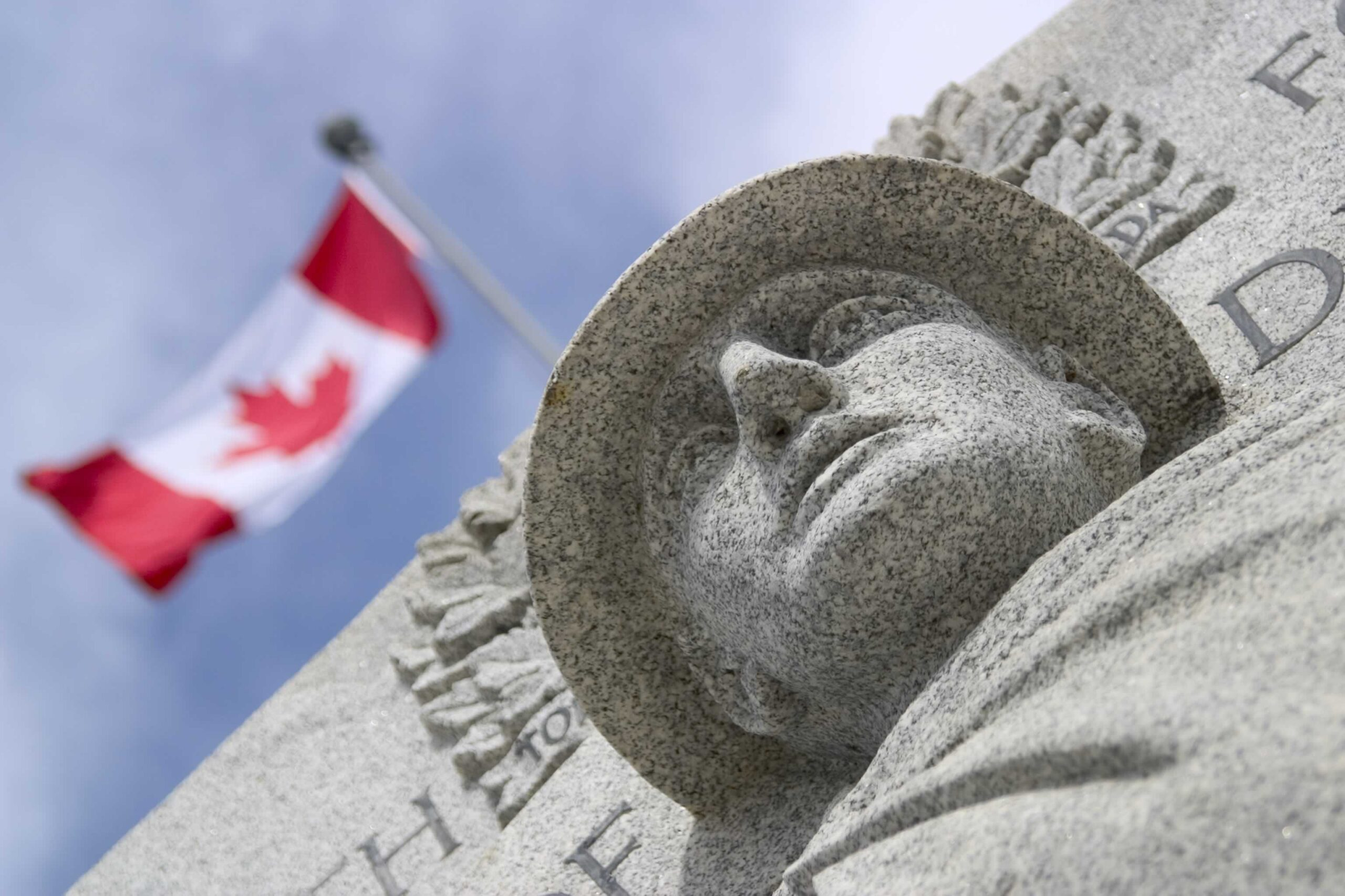 War memorial with Canadian flag in the background.