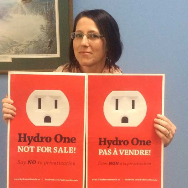 We Own It member mobilizer Carole Gregorcic holding Hydro One Not For Sale signs