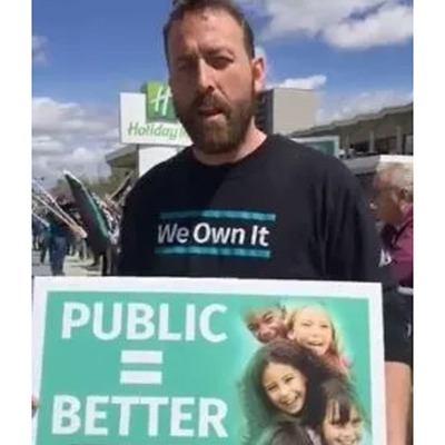 """OPSEU member holds """"Public = Better"""" sign during We Own It rally in Sudbury"""
