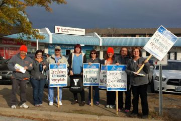 Group of striking CarePartners nurses holding signs picket YMCA job fair in St. Catharines