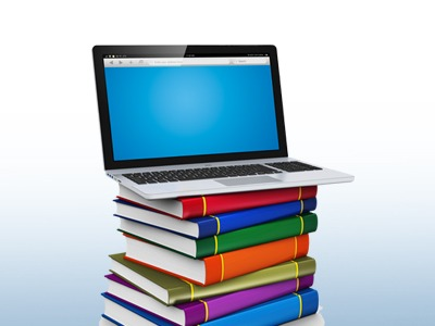 Computer sitting on top of pile of textbooks
