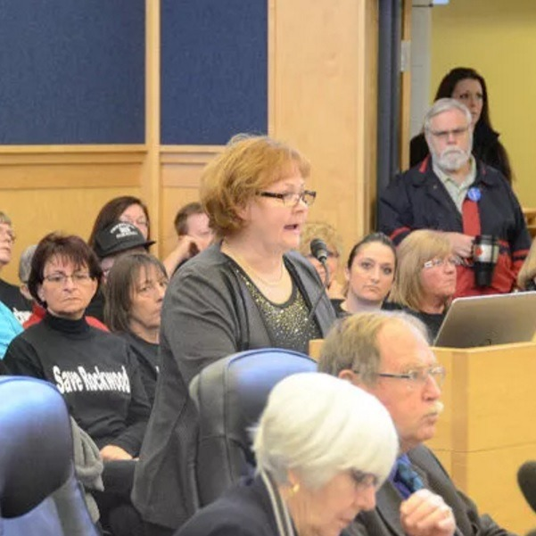 Woman speaks at a microphone during crowded Grey County Council meeting