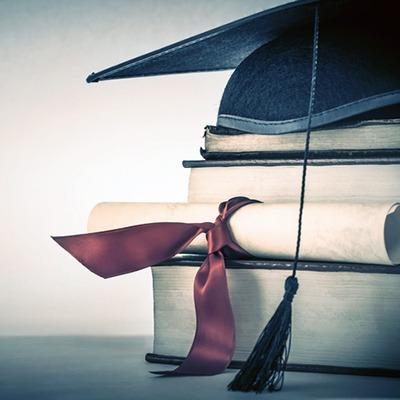 Grad cap and diploma atop textbooks