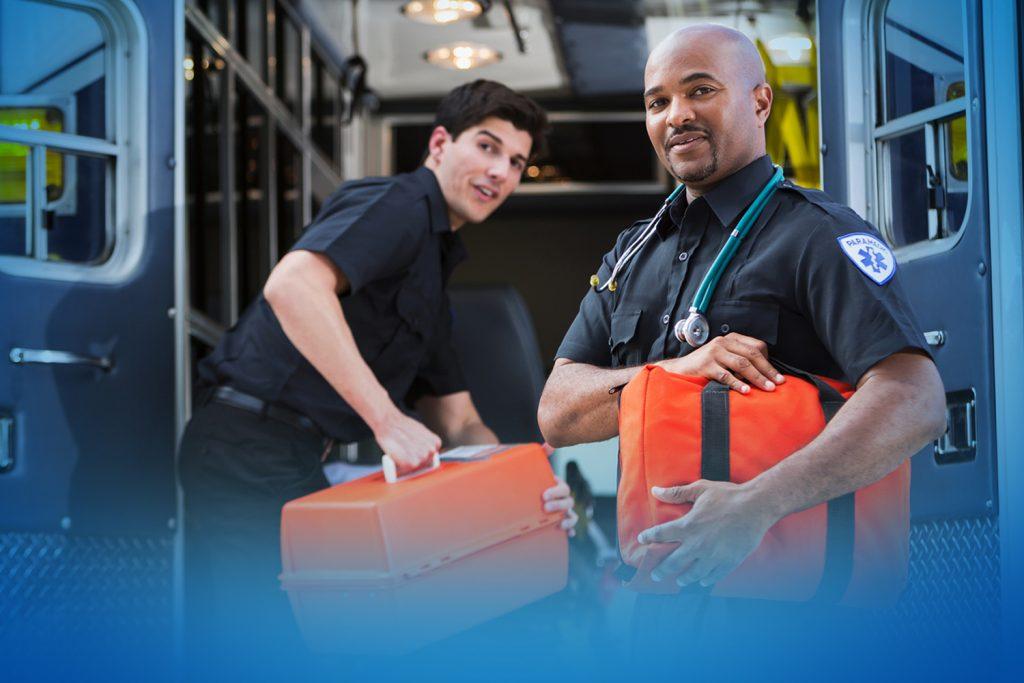 Two paramedics holding medical gear behind an ambulance