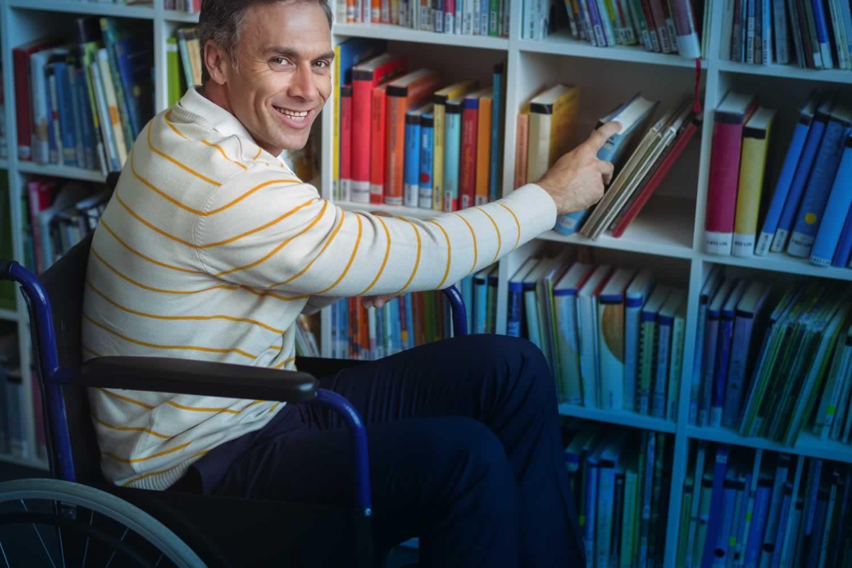 Professor holding books by bookshelf