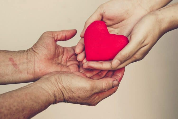 One person holding a heart in their hands, another set of hands underneath holding
