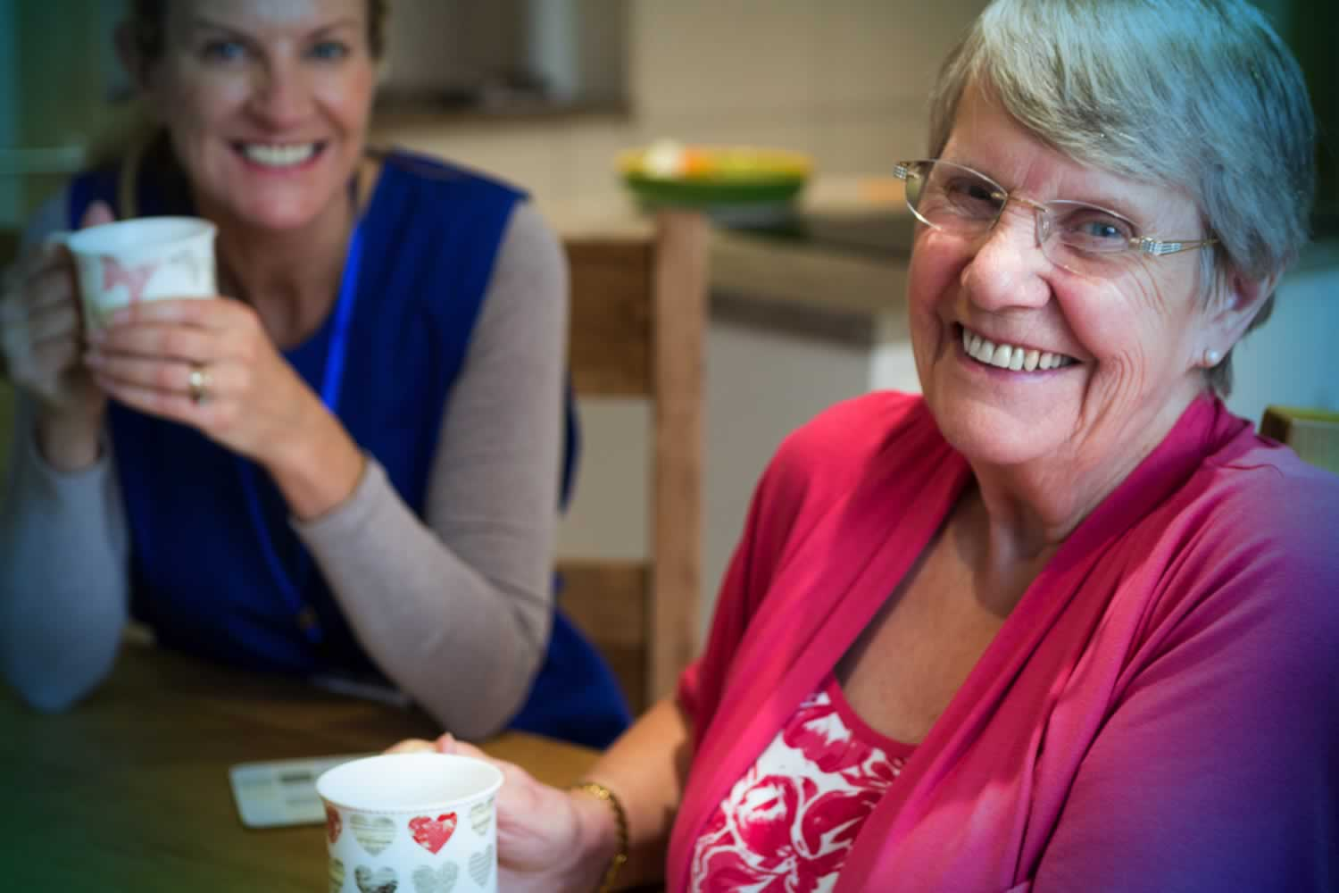 older woman and younger woman sitting together with coffee cups in their hand, smiling