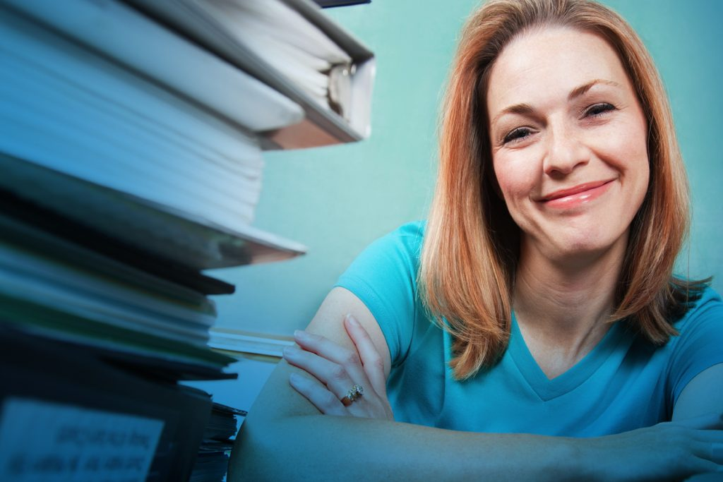 Woman smiling beside stack of books