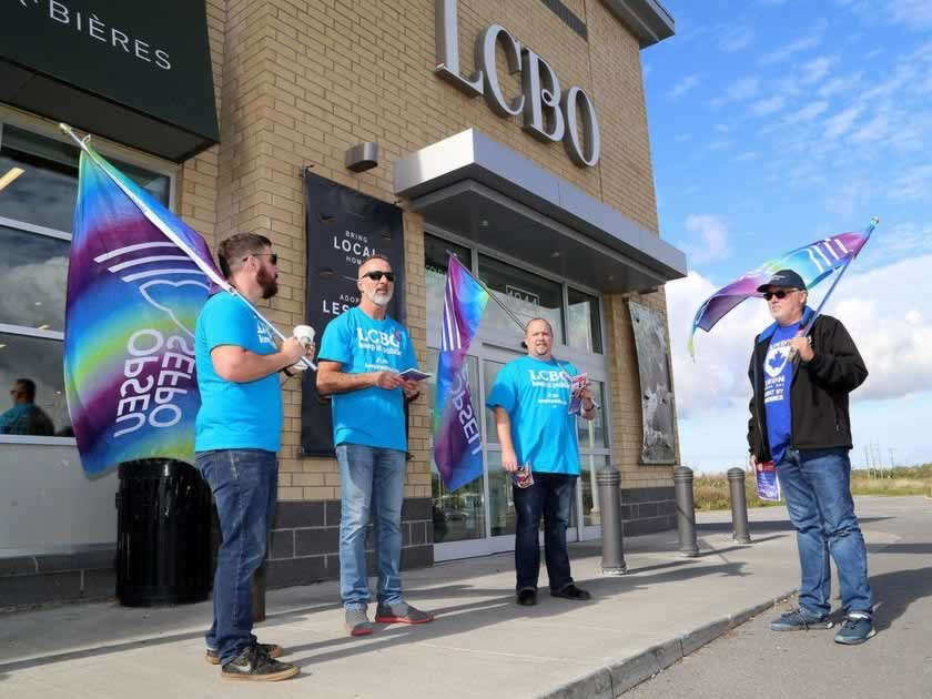 Four men standing holding OPSEU flags standing outside an LCBO entrance