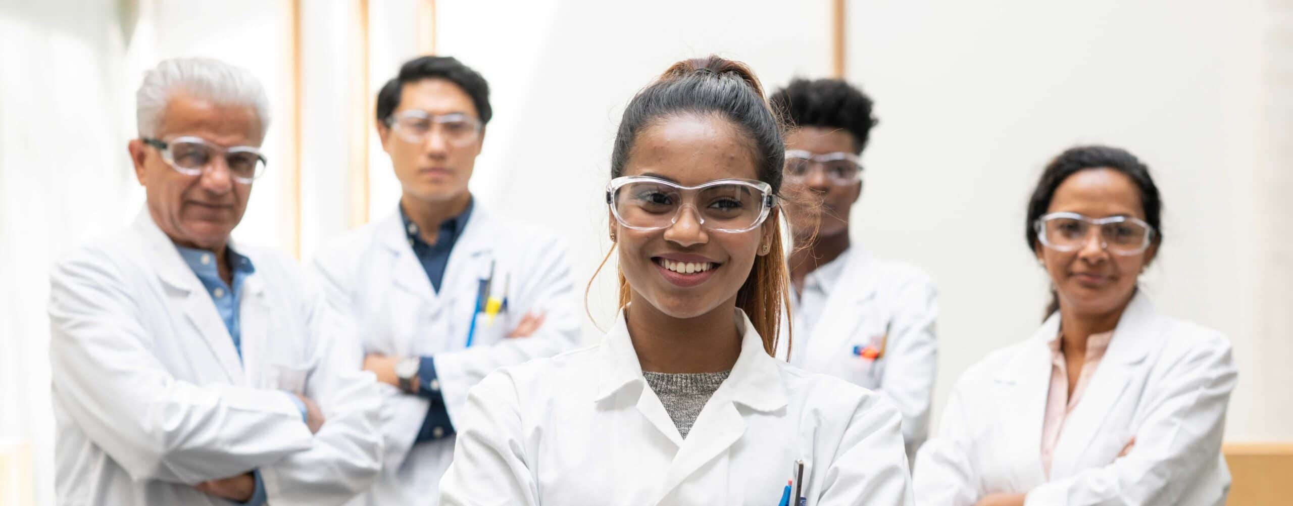 A multi-ethnic group of medical scientists stop and pause for a team portrait before continuing their work. They are each smiling while wearing lab coats and protective eye wear for safety.
