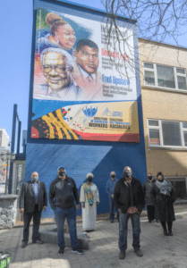 Group of people in face masks standing in front of banner outside building
