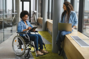 Woman in a wheelchair uses a tablet as another woman uses a laptop