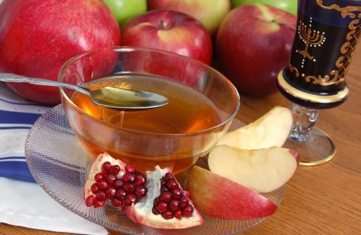 Apples, pomegranate, and honey arranged for a Rosh Hashanah celebration.