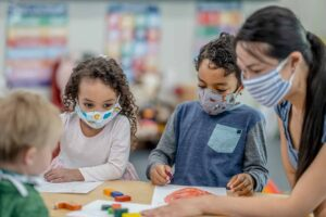 Multi-ethnic group of children and childcare worker colouring at a table while wearing protective face masks to avoid the transfer of germs.